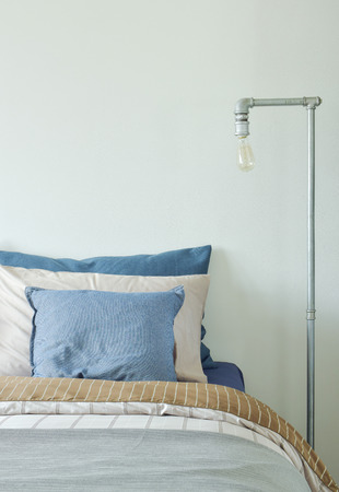reading lamp: Industrial style reading lamp next to bed in blue and gray color scheme bedding