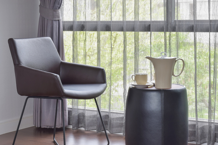 easy chair: Ceramic coffee set on the table with black leather easy chair in living room