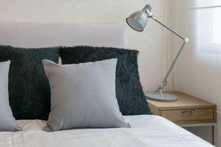 bedroom design: bedroom interior design with grey pillows on white bed and decorative table lamp. Stock Photo