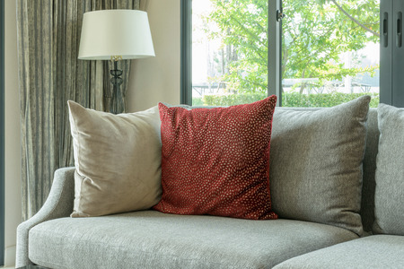 red pillows: modern living room with red pillows on gray sofa and decorative lamp