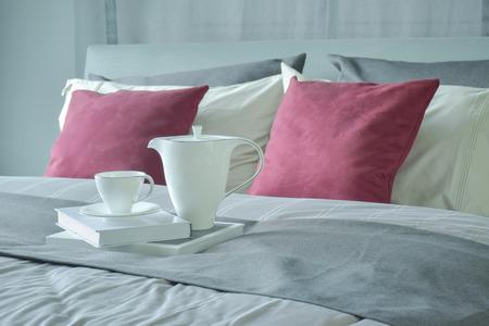 Keramik-Tee-Set und Bücher auf dem Bett mit roten Samtkissen Einstellung Lizenzfreie Bilder