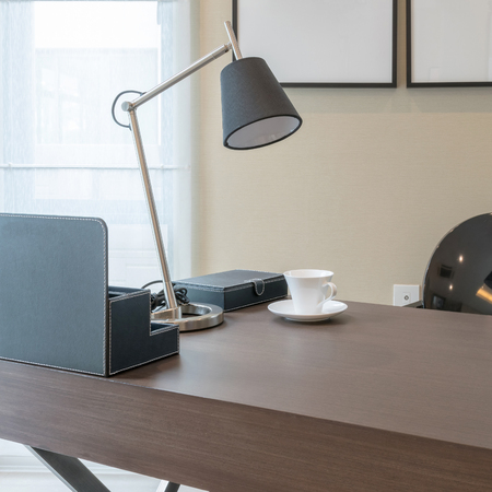 tea lamp: wooden table with reading lamp and tea cup in modern working room interior