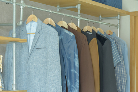 walk in closet: Men casual suits hanging in modern industrial style walk in closet
