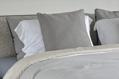 comfy: Gray pillow on white setting on bed with comfy blanket