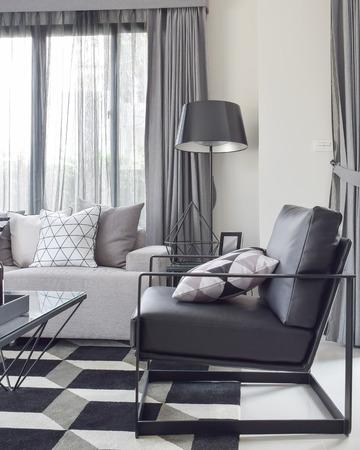Black armchair with geometric rug in modern living corner