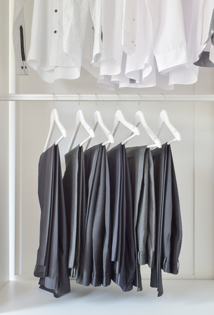 black pants: row of white shirts and black pants hanging in wooden wardrobe