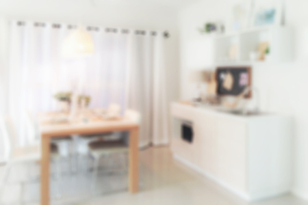 pantry: Defocus wooden dining table next to pantry in modern kitchen