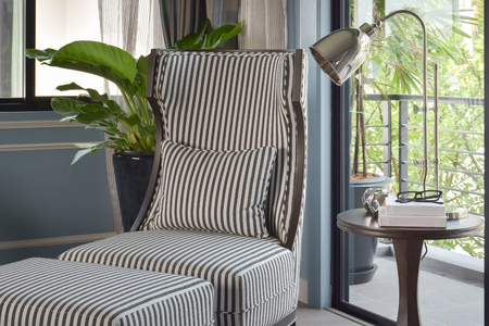 easy chair: Striped high back easy chair with brass table lamp in the living room