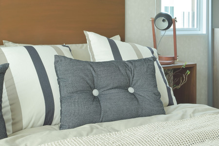 headboard: Gray and brown strip pillows setting on bed with brown headboard
