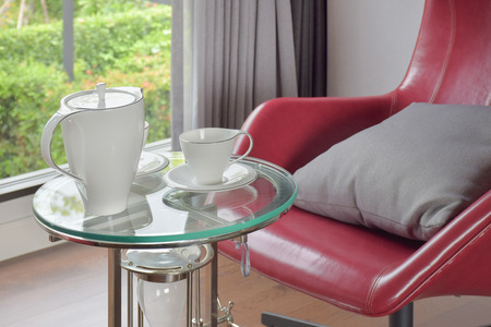 easy chair: Tea set on glass top table with red easy chair in living room
