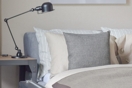 side table: Gray, beige and stripped pillows setting on bed with black reading lamp on bed side table Stock Photo