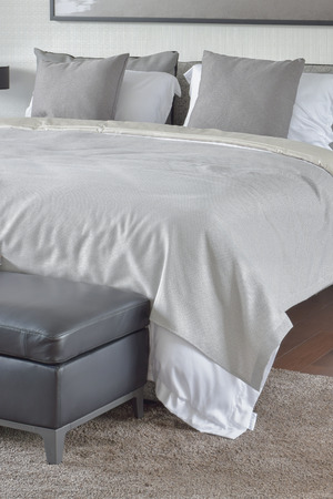 comfy: Beige blanket on comfy bed with black leather ottoman