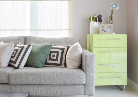 sideboard: Cozy sofa with geometric pattern pillows and green sideboard in living corner
