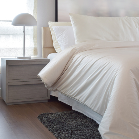 carpet clean: Cozy bedroom interior with pillows and reading lamp on bedside table Stock Photo