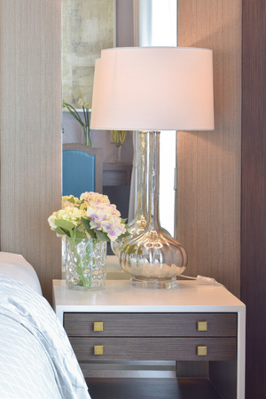 bedside: reading lamp on bedside table in classic bedroom