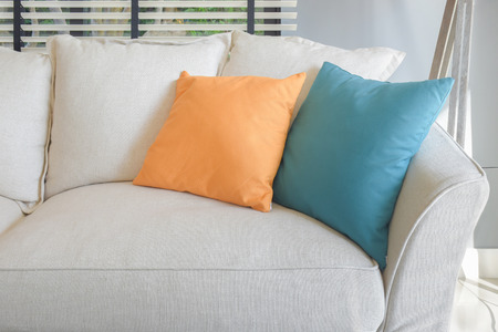 room accent: Yellow and green pillow on white sofa set