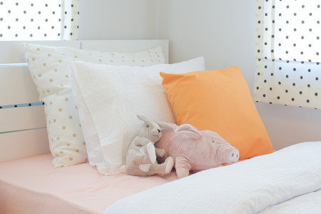 Piggy und Kaninchen Puppe Einstellung auf dem Bett neben orange Farbe Kissen im Schlafzimmer Cutie Stil