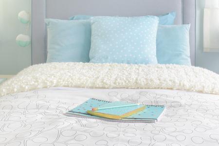 biege: light blue notebooks setting on biege color blanket with light blue interior bedroom