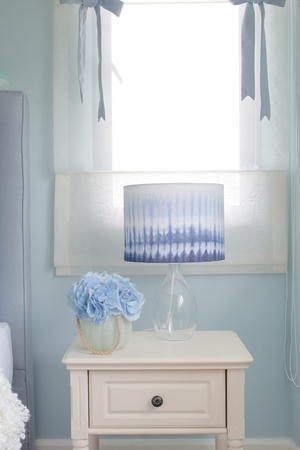 reading lamp: Flower jar and reading lamp on bedside table in light blue interior bedroom Stock Photo