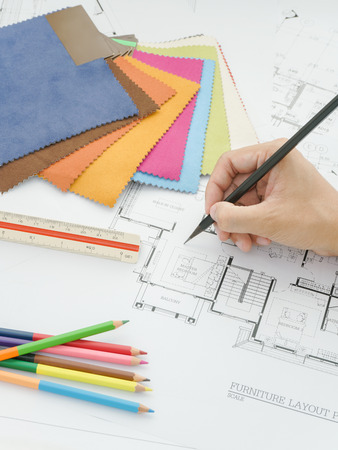 color scale: View of hand writing  on architectural drawing with fabric sample, scale and color pencil Stock Photo