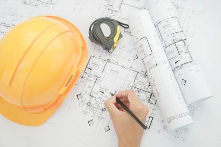 architect tools: Architect working on construction blueprint. Architects workplace - architectural project, blueprints, helmet, measuring tape, Construction concept. Engineering tools. Top view