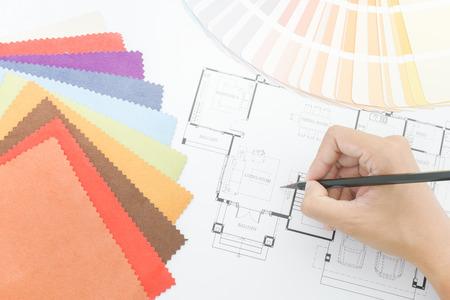 pallette: Close up main qui écrit sur le dessin architectural avec palette de couleurs et de l'échantillon de tissu Banque d'images