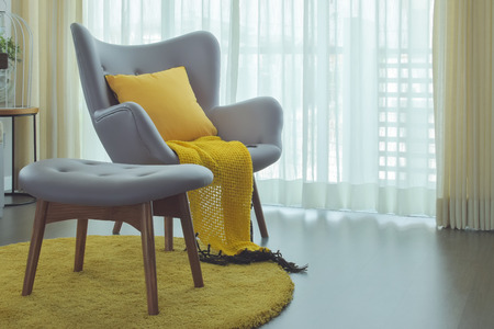 Easy armchair in gray color with scarft, pillow and area rug in yellow color scheme