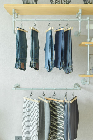 walk in closet: Skirts and jeans hanging in industrial style walk in closet