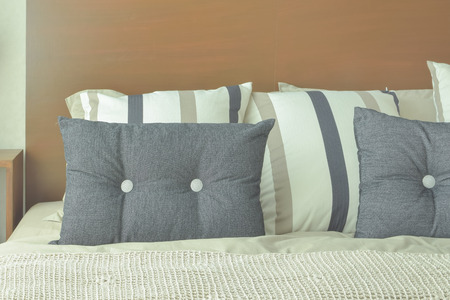 king size: Gray and brown strip pillows setting on bed with brown headboard