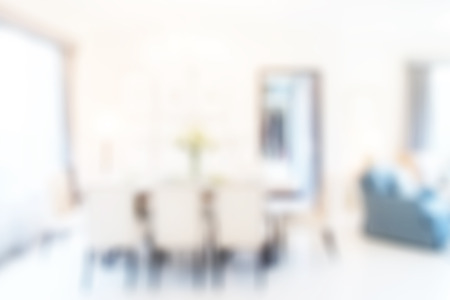 Blurred dining table next to sofa set in modern interior multi