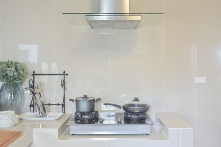 stainless steel range: stainless pan on gas stove with utensil in modern kitchen