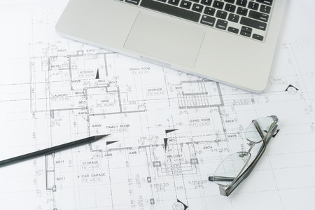 black pencil and computer laptop on architectural drawing paper for construction Standard-Bild