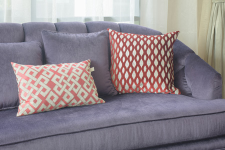 red sofa: Red pattern pillows lay on violet sofa in living room