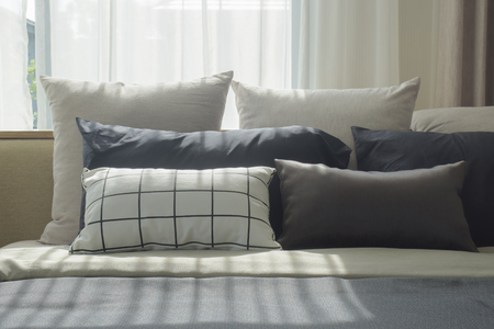Varies size of pillows setting on bed with natural light in bedroom