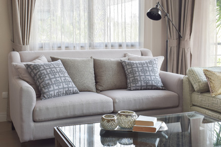 stool: Books on glass top table and gray tone sofa set in modern living room