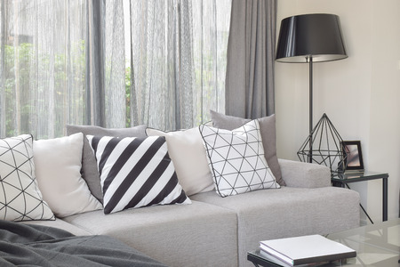 Varies pattern pillows in monotone setting on light gray sofa with black standing lamp Banco de Imagens