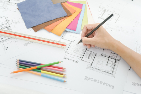 architect: Hand writing on architectural plan with fabric sample on interior designer working table