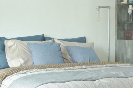 bed sheet: Blue and gray color scheme bedding with reading lamp