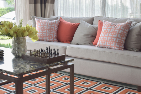 stool: Graphic orange scheme pillows and graphic orange carpet in living room Stock Photo