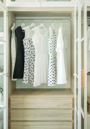 suite: White wooden closet with row of dress and blouses Stock Photo
