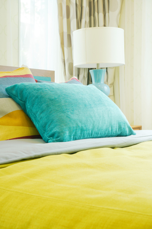 luxury room: Green pillow on bed with yellow blanket Stock Photo