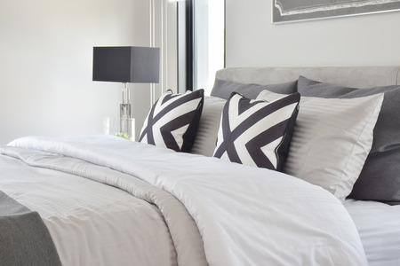 bedside: Graphic style pillows on on classic color bedding with black reading lamp Stock Photo