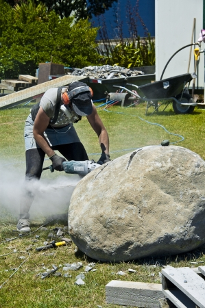stone cutter: Artist cutting large stone for sculpture Stock Photo