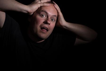 Man in shock holding his head . Low key portrait. photo