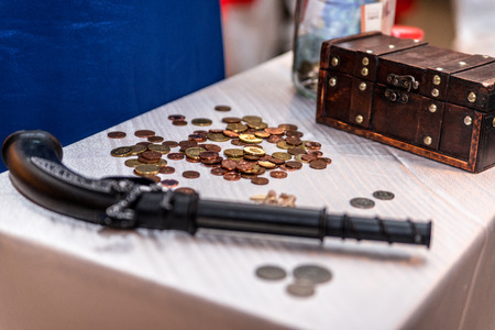 old desk: Old pistol, coins and a box on the desk
