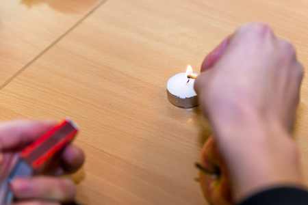 Hands ignited white candle with matches on top of table