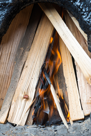 ignition: Briquettes for ignition among the firewood, begin of burning Stock Photo