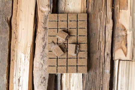 Briquettes for firing, ignition on the background of wood. View from above Stock Photo