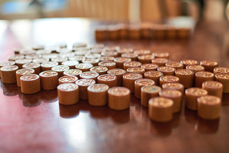 allegoric: Lotto game kegs on wood board composition, side lighting