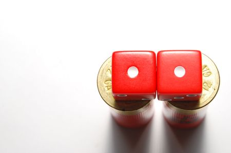 Two dice lying on 12 guage shotgun shells. Dice showing snake-eyes with focus on top of shells. Stock Photo